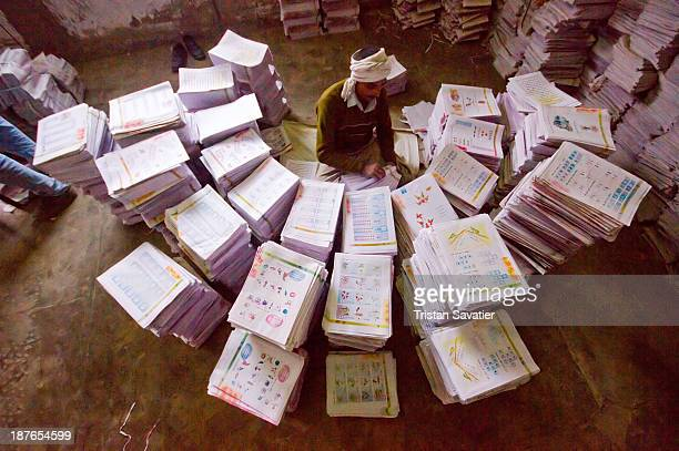 Print shop worker collating printed leaflets into booklets. The booklets produced in this print shop are Indian school books. This simple mechanical...