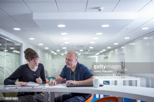 print worker discussing print job with client in print factory - factory stock pictures, royalty-free photos & images