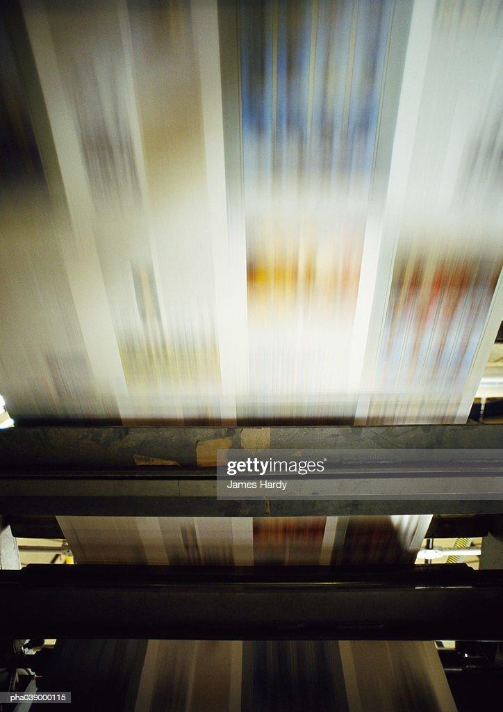 Printed paper on printing press, blurred motion : Stockfoto