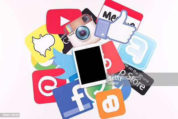 Bedrucktes Papier Social Media-Logos auf Schreibtisch mit Mobile Geräte
