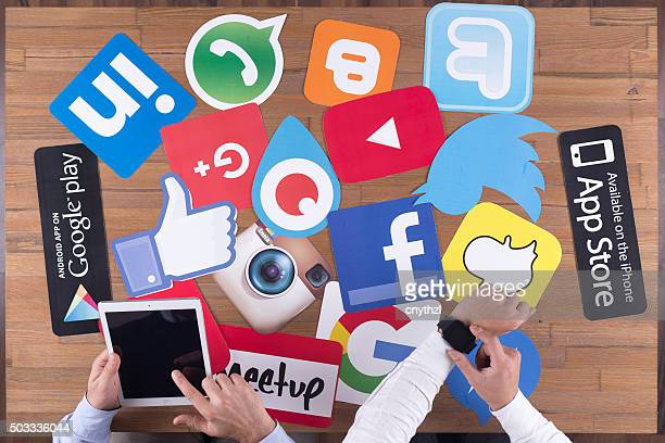 Printed Paper Social Media Logos on Desk with Users