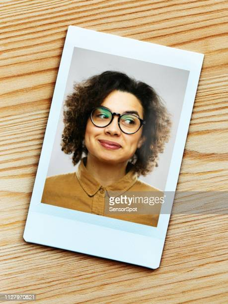 printed portrait of young happy woman from instant camera looking away. - graphic print stock pictures, royalty-free photos & images