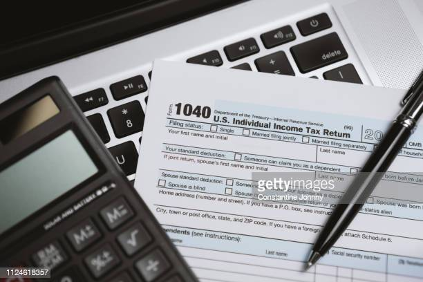 printed tax form on laptop with calculator and pen - 1040 tax form stock photos and pictures