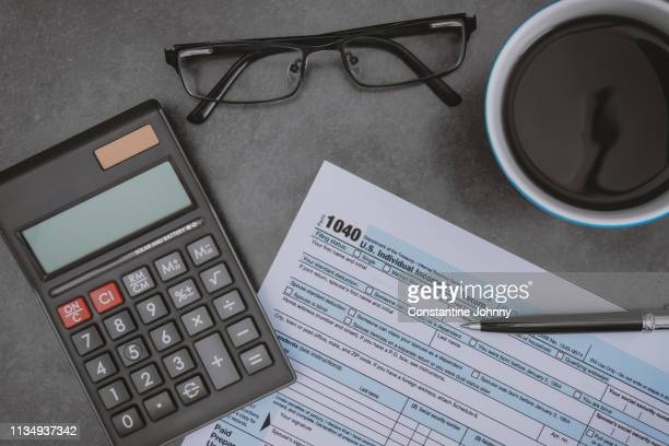 printed tax form on work desk with calculator and pen - filing documents stock pictures, royalty-free photos & images