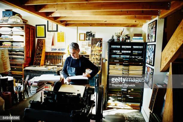 Printer at letterpress preparing to print cards