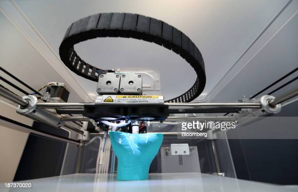 A 3D printer builds a replica of a human hand during the 3D Print show at the Business Design Center in London UK on Friday Nov 8 2013 Popularity for...
