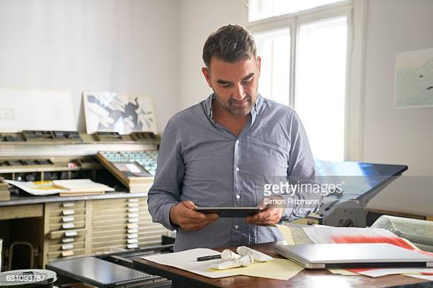 Printer using digital tablet in his workshop