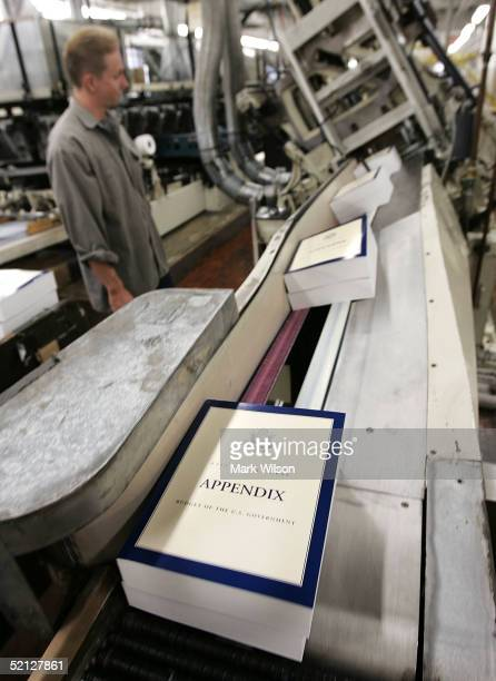 A printer watches as copies of the fiscal year 2005 budget come out of a binding machine at the Government Printing Office February 3 2005 in...