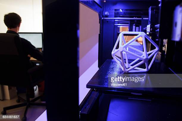 3D printers and man working with a computer