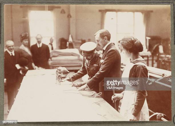 Printing out paper print Photograph by Horace W Nicholls of the visit of King George V and Queen Mary to a factory manufacturing soldiers' uniforms...