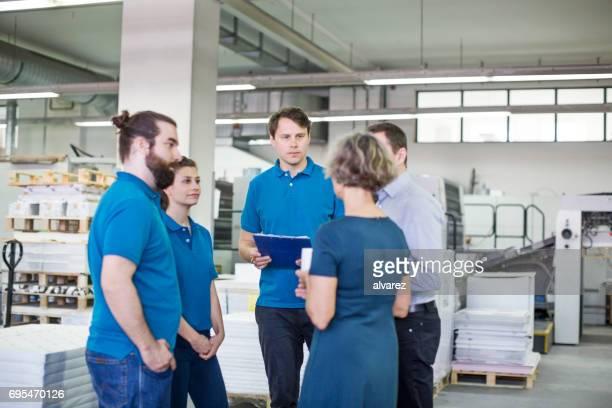 Druckmaschine Arbeiter Team mit treffen im Werk