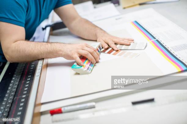printing press worker with color swatch - printing plant stock pictures, royalty-free photos & images