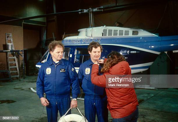 Prior to an television interview in a hanger as US Park Police paramedic Gene Windsor watches an unidentified woman attaches a microphone to Windor's...