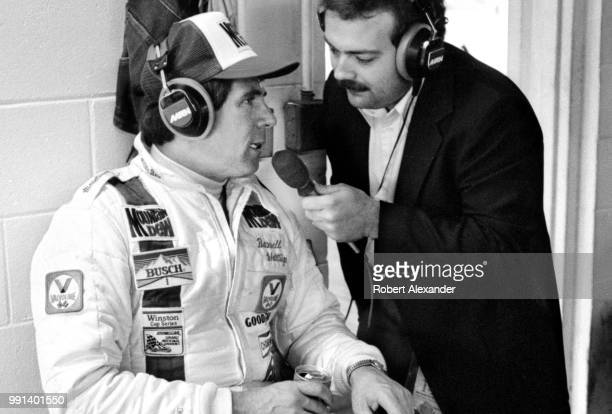 Prior to the start of the 1982 Daytona 500 auto race NASCAR driver Darrell Waltrip is interviewed by MRN radio reporter Dr Jerry Punch in the garage...