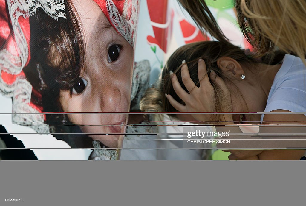 Priscilia, 27, whose daughter Geovanna Vitoria de Barros, 1, was shot dead last Friday 18 during a robbery attack while on their car in Baixo Fluminense, cries in front of a picture during a tribute on Copacabana beach in Rio de Janeiro on January 21, 2013.