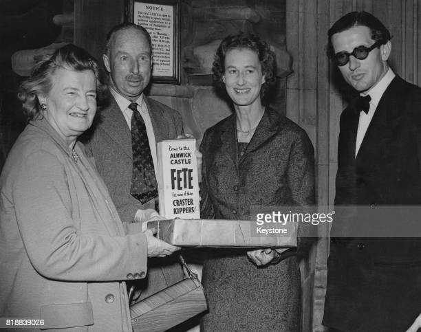 Priscilla Buchan Baroness Tweedsmuir the MP for South Aberdeen is presented with a box of kippers by Sir John Craster at the House of Commons in...