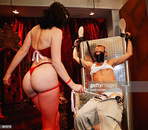 Priscilla Jane uses a riding crop to strike and tease Tom Taylor while he is strapped to a diamond plate throne to demonstrate bondage products for...