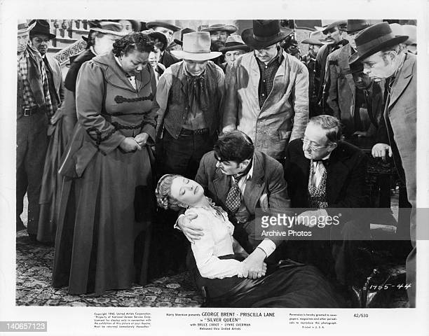 Priscilla Lane lays in arms of George Brent while onlookers surround them in a scene from the film 'Silver Queen' 1942