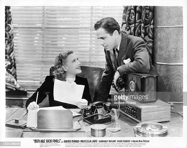 Priscilla Lane looks up at Humphrey Bogart in a scene from the film 'Men Are Such Fools' 1938