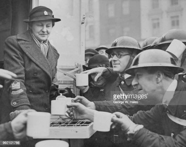 Priscilla Norman née Reyntiens the wife of Montagu Collet Norman Governor of the Bank of England serves tea to ARP personnel after handing over a new...