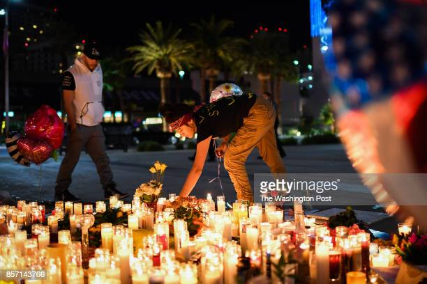 Priscilla Olivas of Las Vegas NV lights up a candle at a street vigil that was held for the victims along the Las Vegas Strip a day after 59 people...