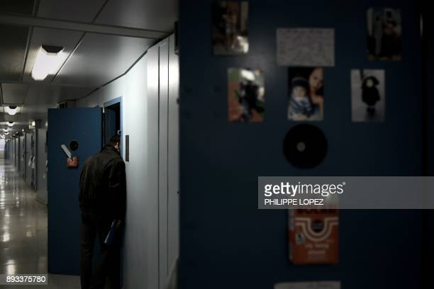 A prison chaplain speaks with an inmate in a cell during a distribution of Christmas gifts by the Christian charity organization 'Secours Catholique'...