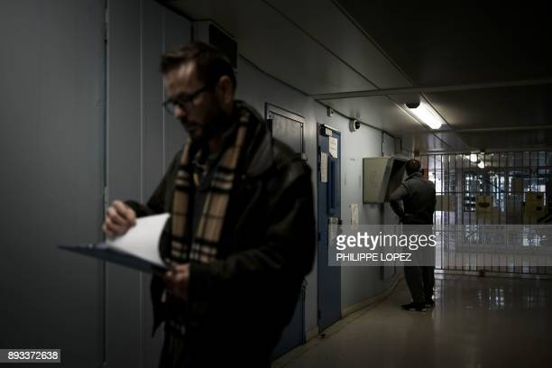 A prison chaplain walks in a corridor during a distribution of Christmas gifts by the Christian charity organization 'Secours Catholique' on December...