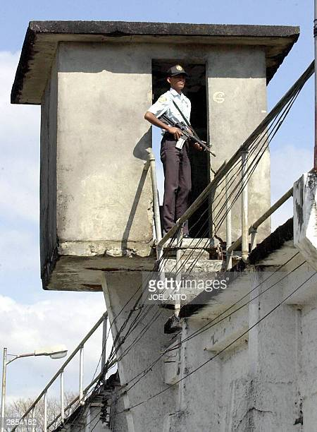 A prison guard at a watchtower looks down at the lethal injection chamber at the Philippine national prison in Manila 09 January 2004 following...