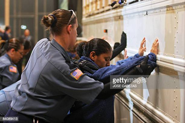 A prison guard frisks a female detainee before embarking onto a bus to be taken to the airport at Willacy Detention facility in Raymondville Texas on...