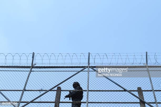 Prison guard keeps watch at the San Francisco Gotera prison, 165 km from San Salvador, on February 16, 2017. In the San Francisco Gotera prison there...