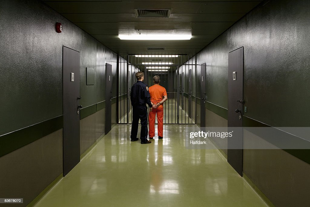 A prison guard leading a prisoner along a corridor : Stock Photo