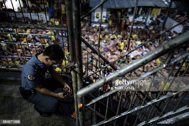 A prison guard locks a gate inside the Quezon City jail at night in Manila in this picture taken on July 21 2016 There are 3800 inmates at the jail...