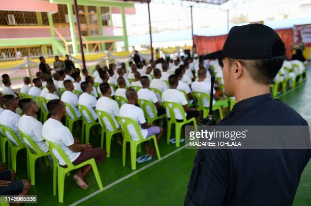 A prison guard looks over prisoners who received royal pardon during a ceremony at the Narathiwat provincial jail in Thailand's southern province of...