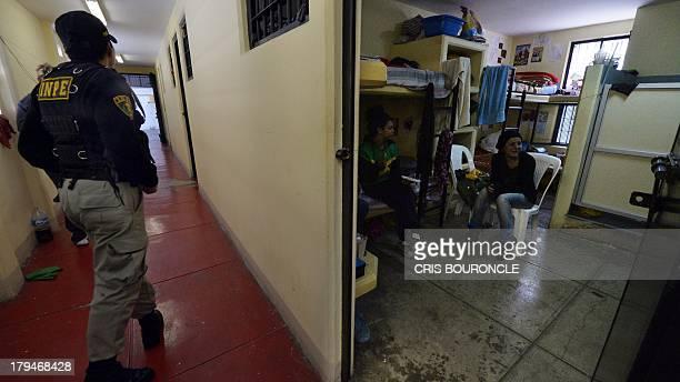 A prison guard walks in a corridor as female prisoners gather in a cell at the Ancon 2 prison part of the Piedras Gordas Model Penitentiary complex...