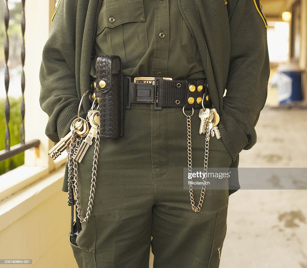 Prison guard with keys on belt (mid section) : Stock Photo