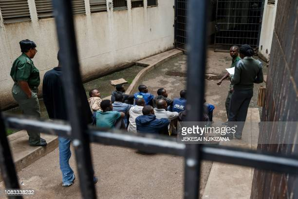 Prison guards of the Zimbabwean Prison Services watch men arrested during violent protests triggered by a sudden rise in fuel prices announced by...