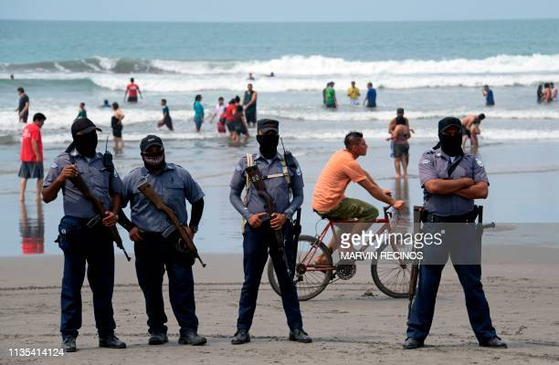 Prison guards stand as Salvadorean lowrisk prison inmates and those in the last stage of their sentences clean the La Costa del Sol beach in San Luis...