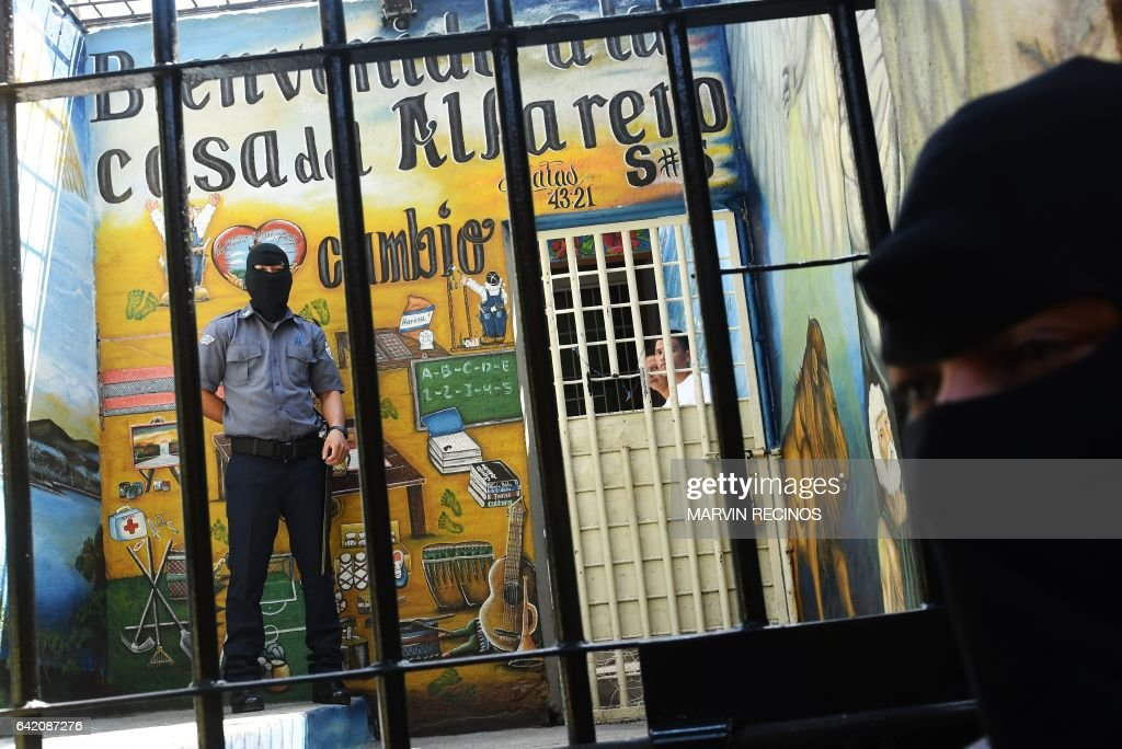 Prison guards wearing balaclavas stand guard at the entrance of the San Francisco Gotera prison, 165 km from San Salvador, on February 16, 2017. In the San Francisco Gotera prison there are 1122 gang members, from whom more than 500 say having abandoned their gangs and feel sorry for their crimes. / AFP PHOTO / Marvin RECINOS