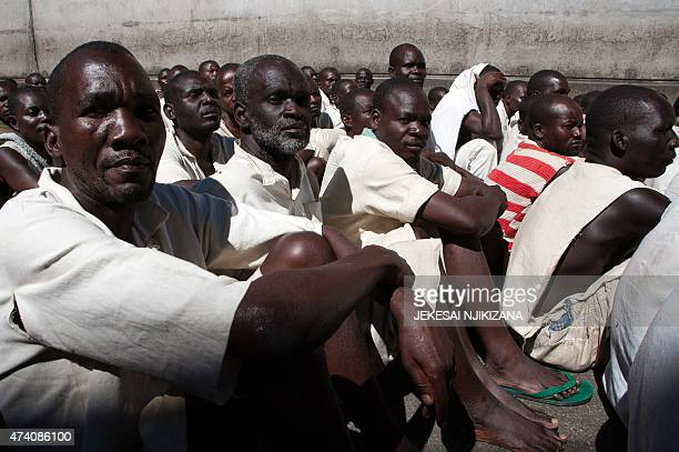 Prison Inmates sit in the yard at the Chikurubi Maximum security prison in Harare Zimbabwe on May 20 2015 during a tour by a parliamentary committee...
