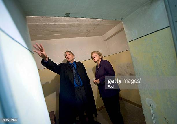 Prison memorial director Hubertus Knabe shows German Chancellor Angela Merkel the former prison of the East German communistera secret police known...