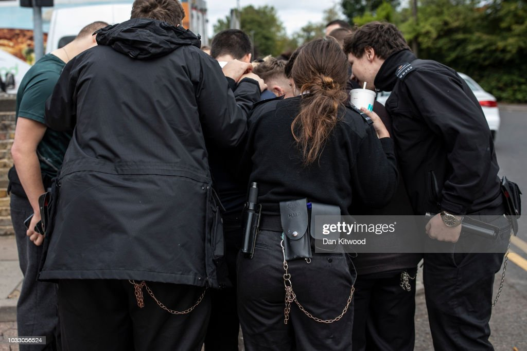 Prison staff at HMP Wandsworth gather outside after staging a 'walk-out' on September 14, 2018 in London, England. The Prison Officers Association called for staff to stage an immediate walk-out this morning demanding the government improve safety in jails and reduce overcrowding and violence among inmates.