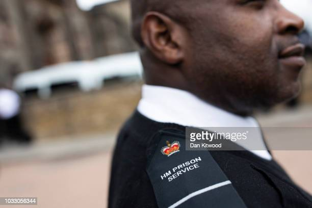 A prison staff at HMP Wandsworth stands as others gather outside after staging a 'walkout' on September 14 2018 in London England The Prison Officers...