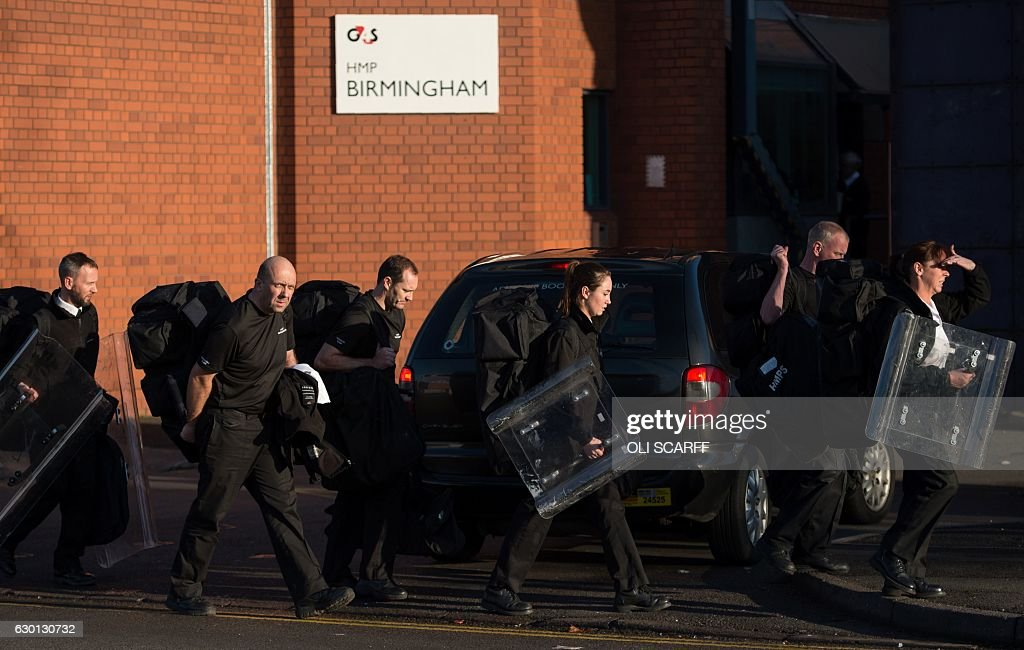 Prison staff carrying riot shields leave HMP Birmingham in Winson Green, Birmingham, central England on December 17, 2016. British riot police, late Friday evening, regained control of a prison after more than 300 inmates took part in a 'serious disturbance' that led to a partial lockdown. A specialist 'Tornado Team', which handles prison riots, was sent in to deal with the incident at the privately run prison in Birmingham, central England. SCARFF