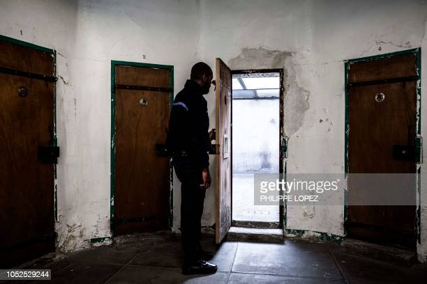 A prison staffer opens a door of an individual courtyard at Fresnes Prison in Fresnes near Paris on October 17 2018