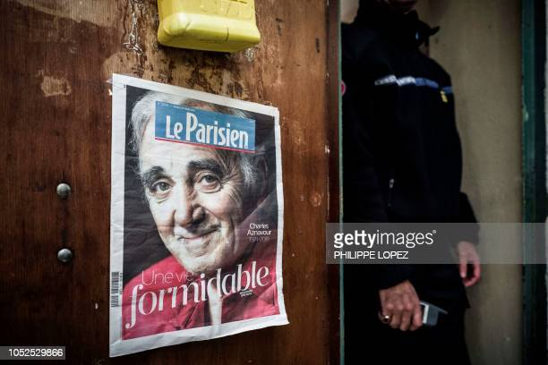 A prison staffer stands next to a cell's door where hangs a photograph of late FrenchArmenian singer Charles Aznavour at Fresnes Prison in Fresnes...