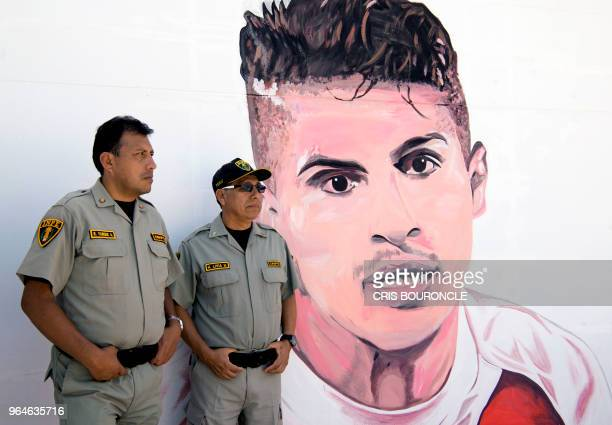 Prison wardens stand guard beside a graffiti depicting Peruvian football star Paolo Guerrero as inmates from Peruvian jails take part in the First...