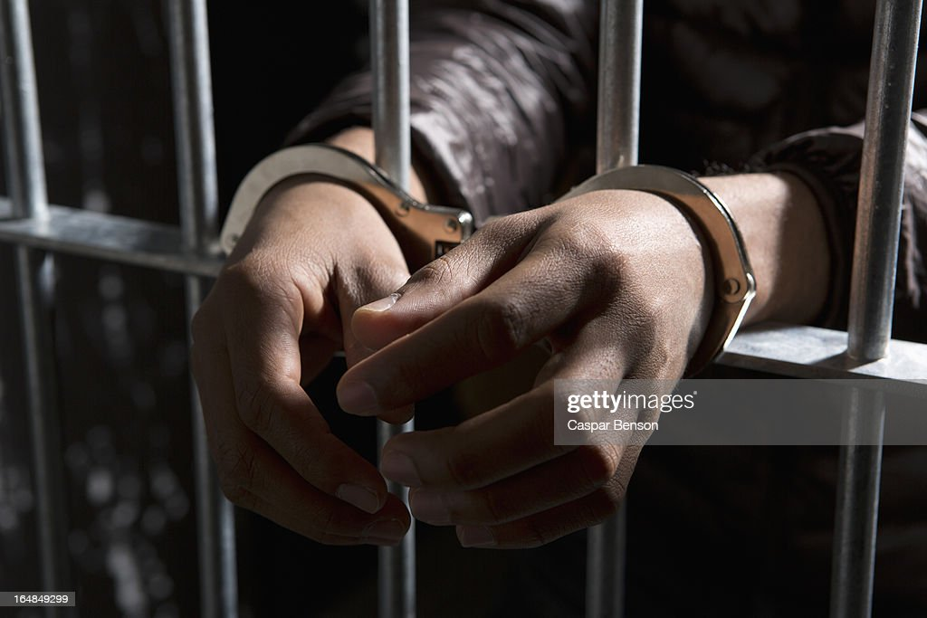 A prisoner behind bars with hands cuffed : Stock Photo