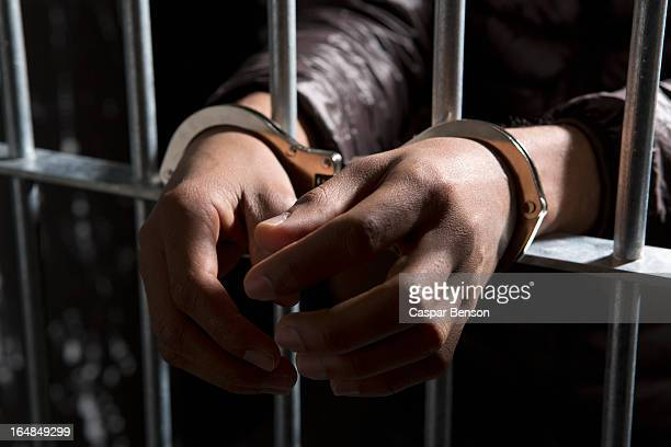 a prisoner behind bars with hands cuffed - handcuffs stock pictures, royalty-free photos & images