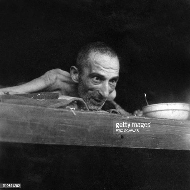 A prisoner dying of dysentery at the Nazi concentration camp of Buchenwald peers out from his bunk in April 1945 upon the liberation of the camp by...