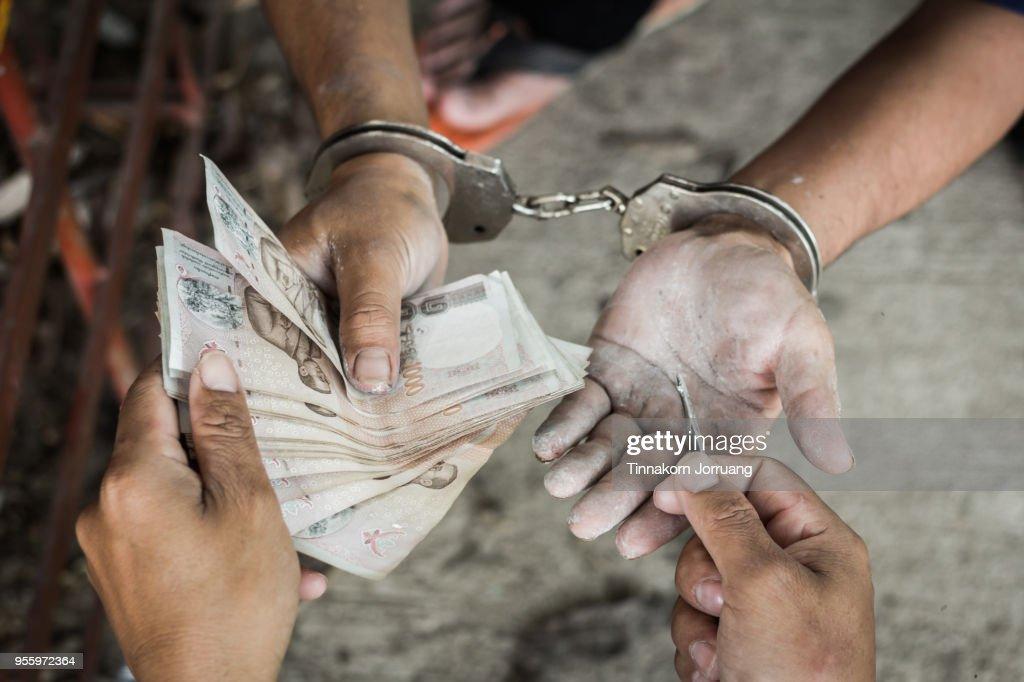 gevangene geld geven voor vrijheid, Hand voor een man in handboeien smeergeld te geven : Stockfoto